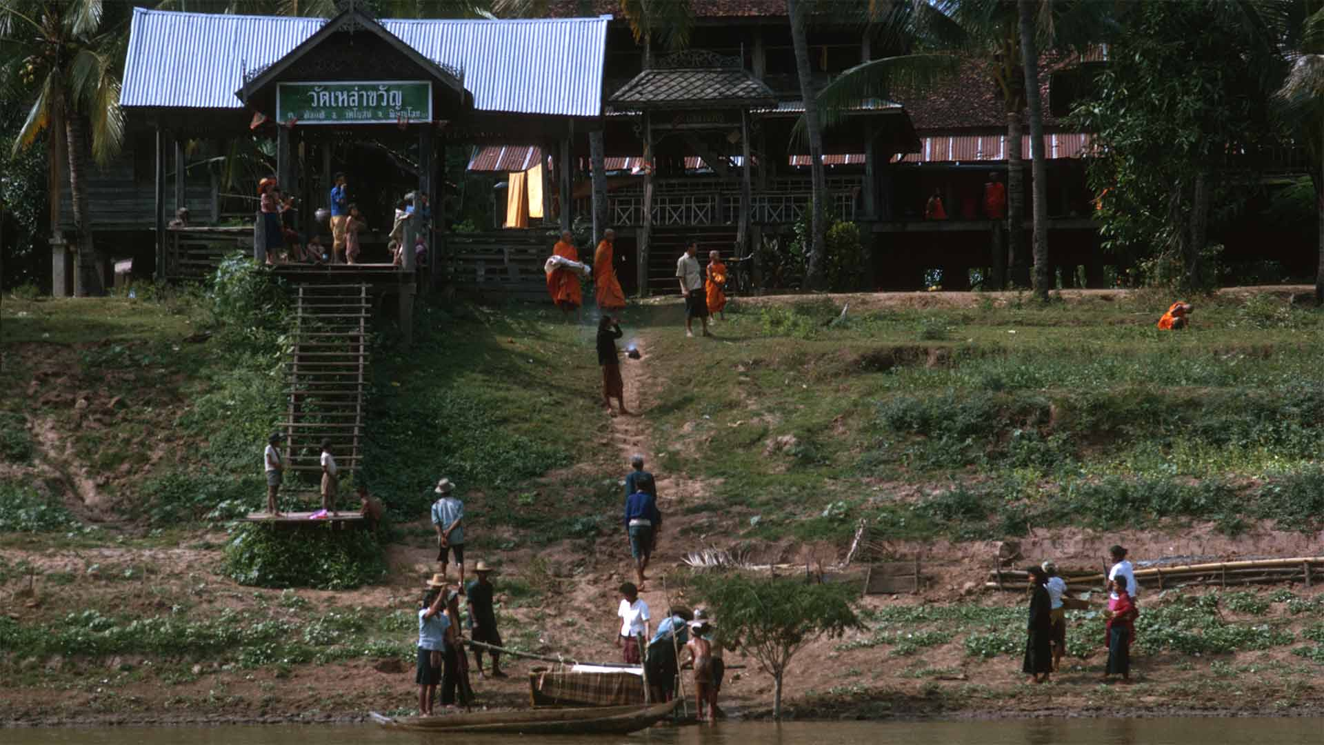 People scattered on a hillside, A coffin sits in a raft on the waterfront.