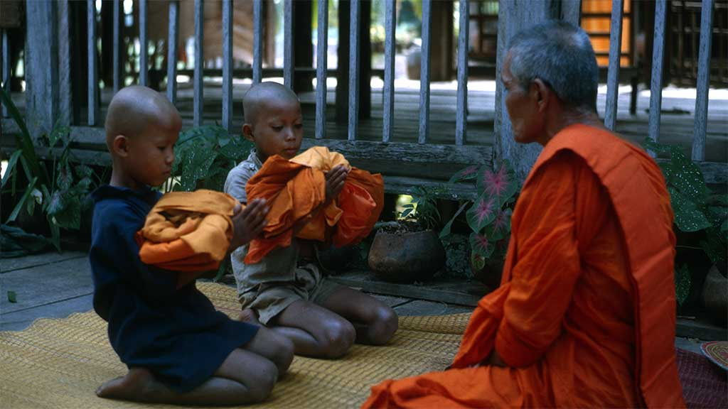 Two boys with shaven heads receive orange robes from an elder monk.