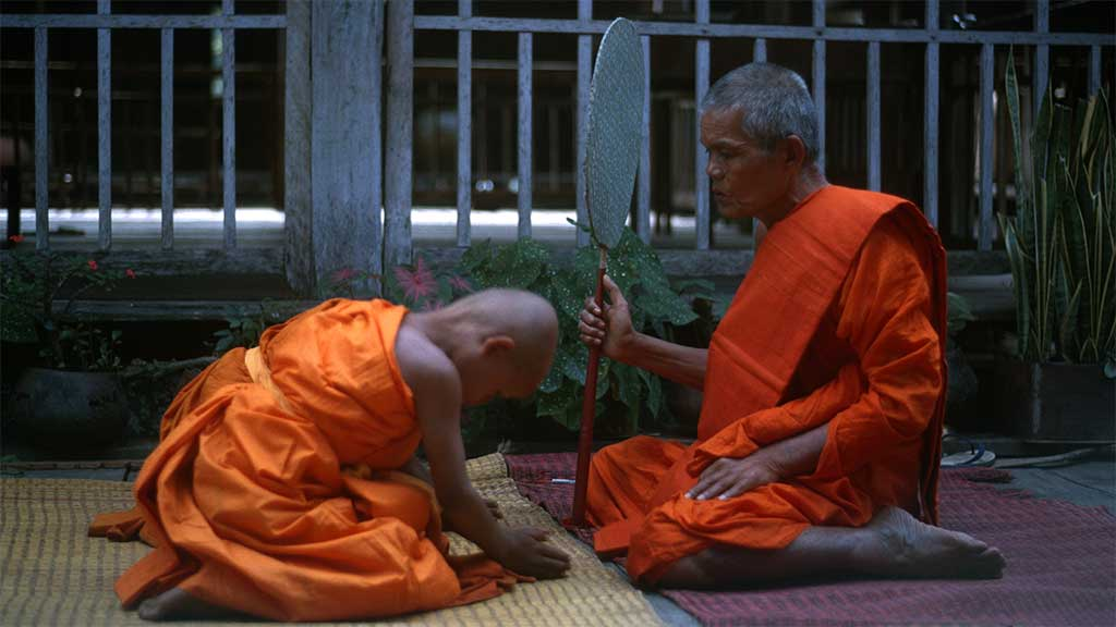 One boy in an orange robes bows his head in front of an elder monk