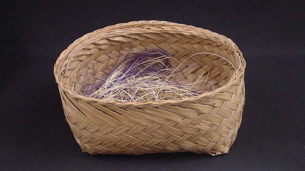 small round women basket filled with purple and cream colored fibers