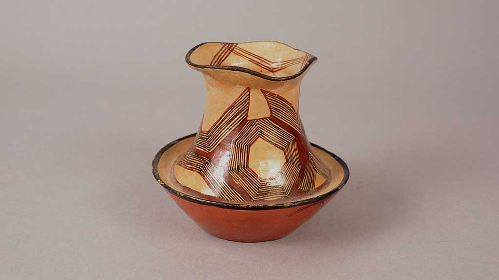 white ceramic vessel with red and black geometic designs