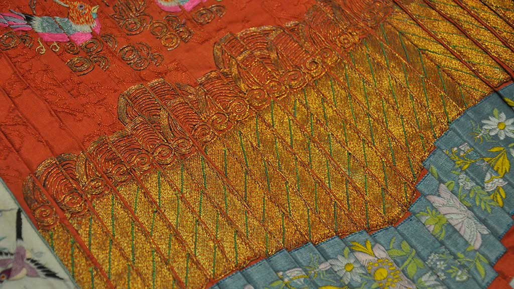 A vibrant textile with red, gold, and blue banding and gold thread