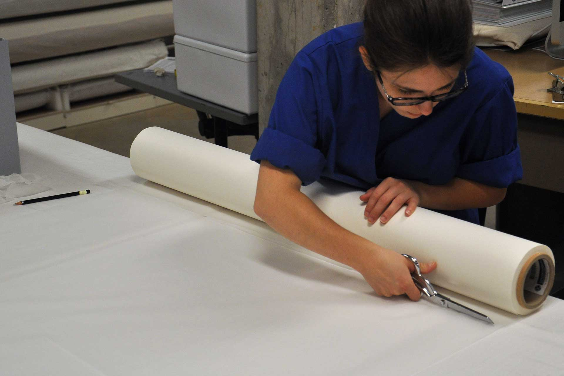 a student cuts paper from a long roll