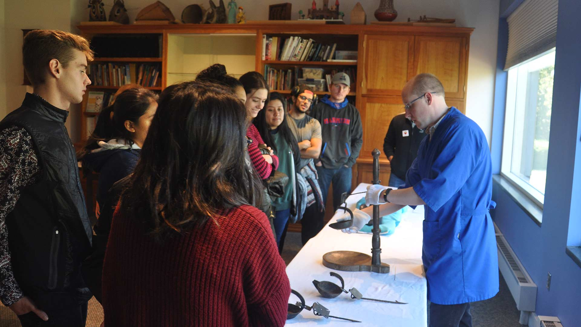 Collections staff member shows a wooden artifact to a group of students