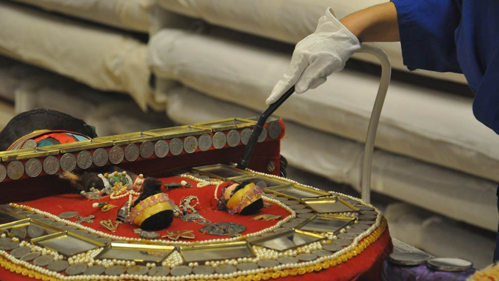 Soffia using a specialized brush tool attached to a commercial vacuum to clean the felt