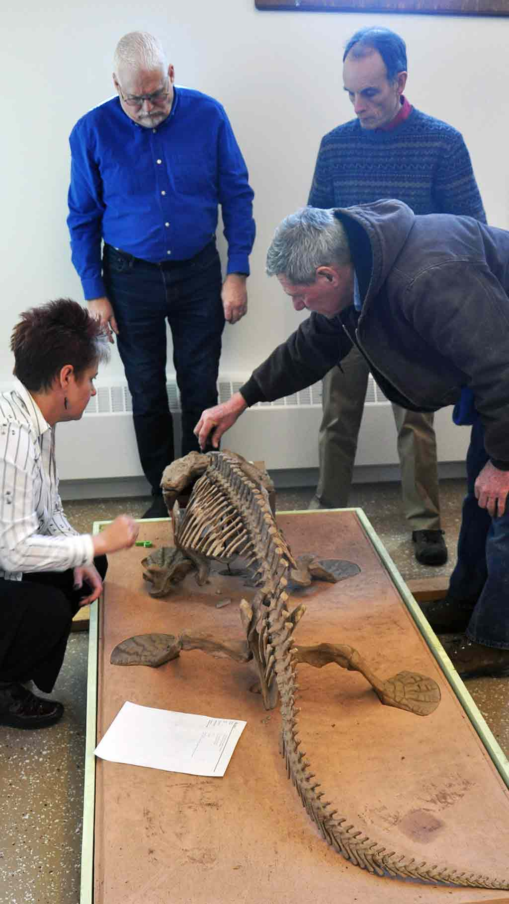 woman and man inspect head of cast of large amphibian