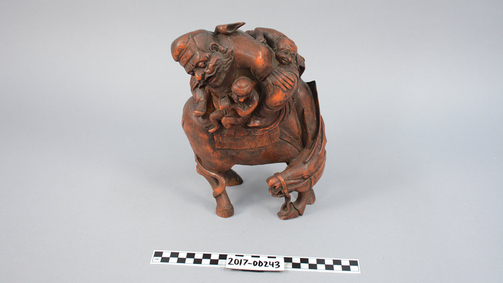 bamboo carving of a man and two small figures on donkey