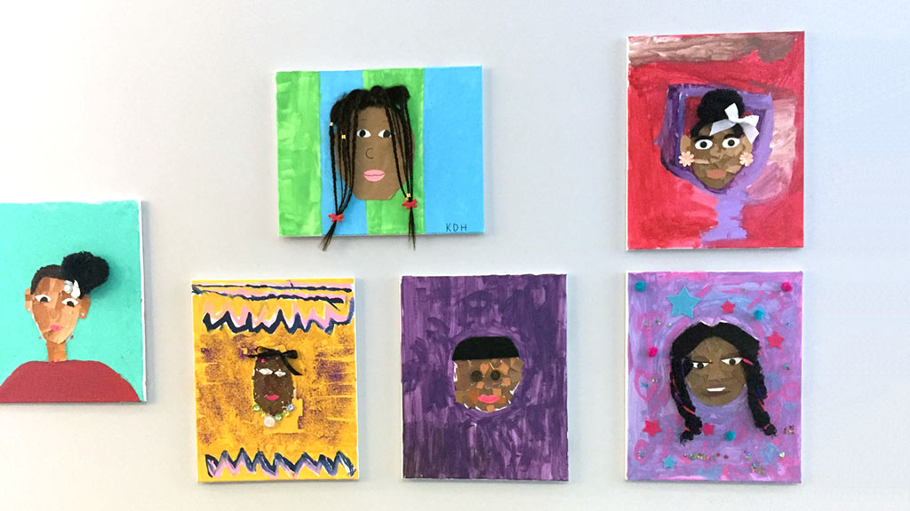 colorful art made by kids hung up in riverfront museum wall