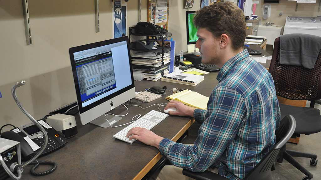 Intern sits at his work station and evaluates the condition of an artifact using an iMac computer.