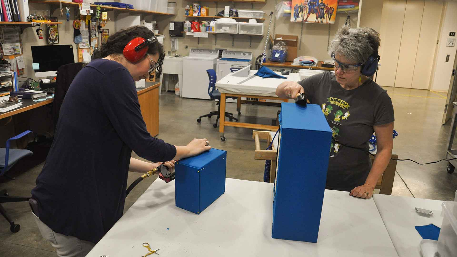 Two staff members in an prep area prepare fabric covered blocks for the exhibit
