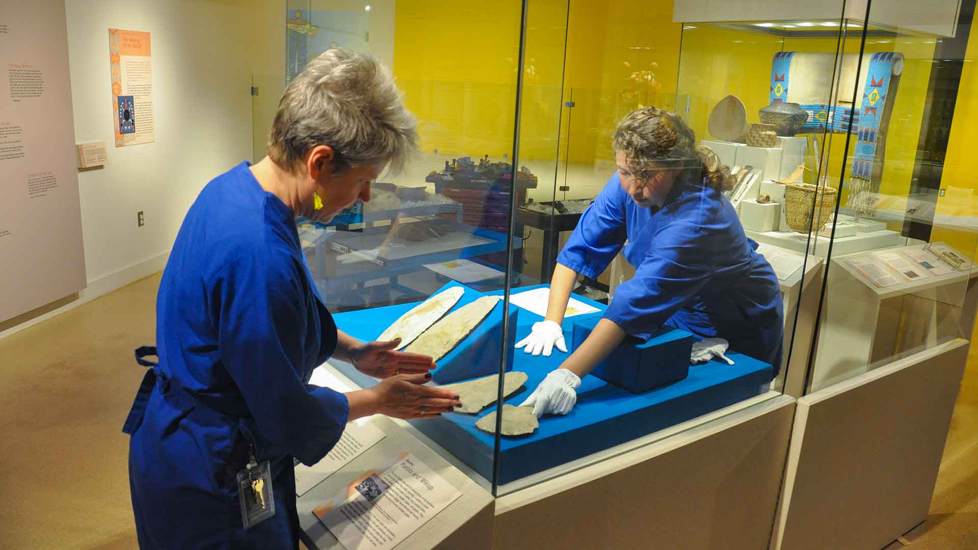 Two staff members arrange objects in the exhibit case in the gallery