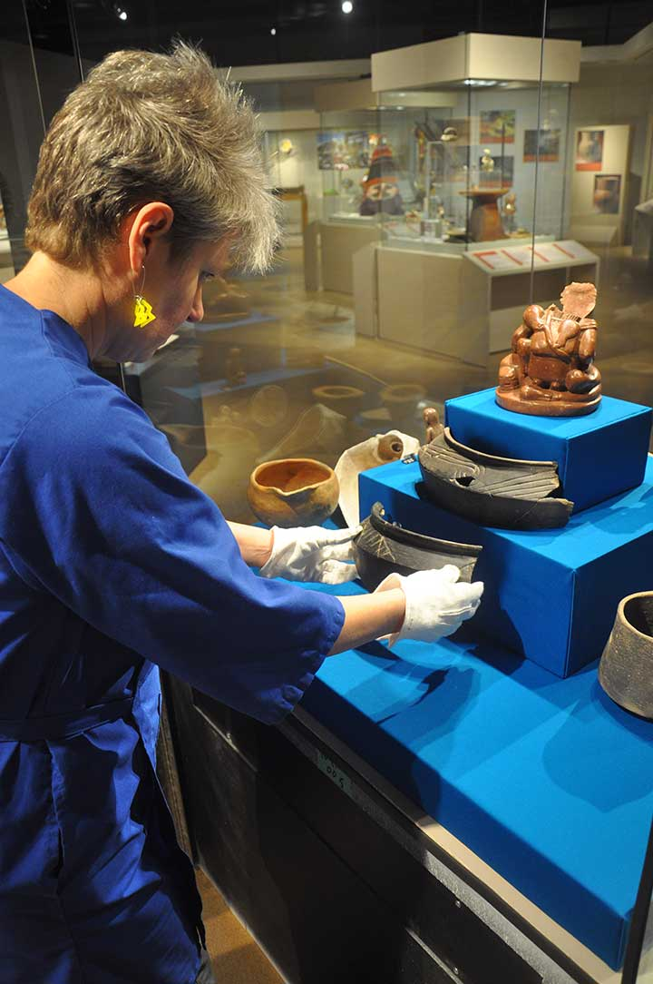 a staff member arranges fragments of a ceramic pot in an exhibit case