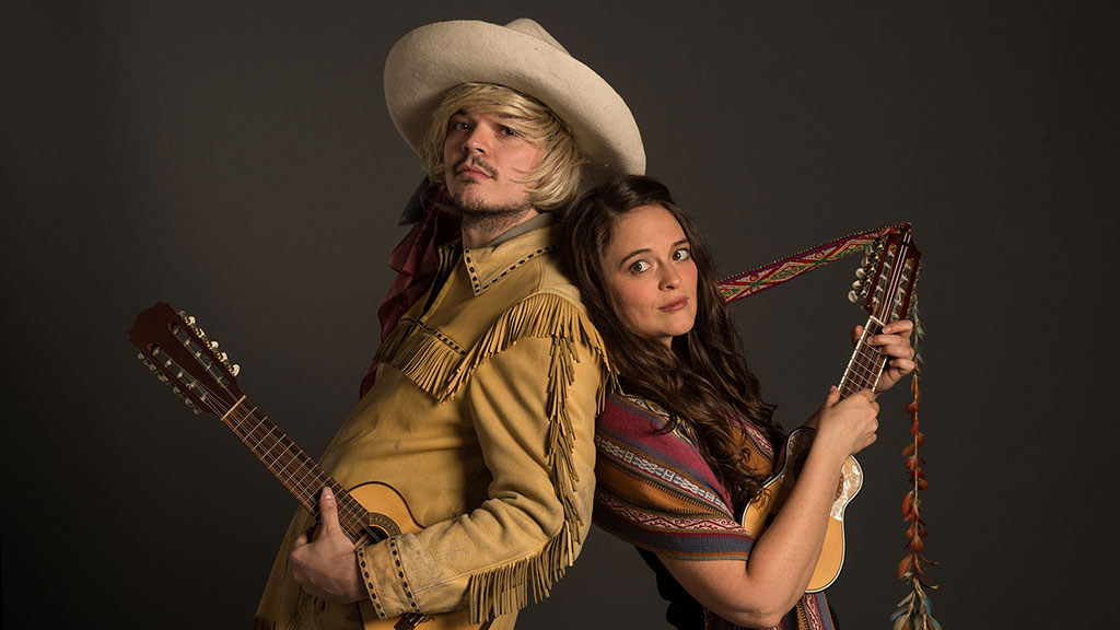 Two musicians, a man and woman, hold guitars in a studio shot. Man is dressed similar to an American cowboy.