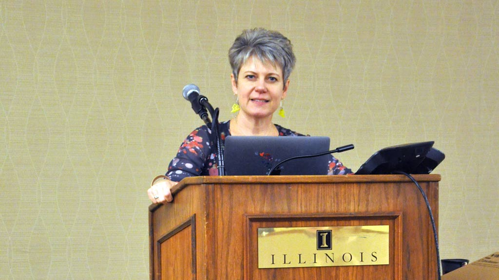Christa standing behind a podium with laptop and microphone while smiling at the camera