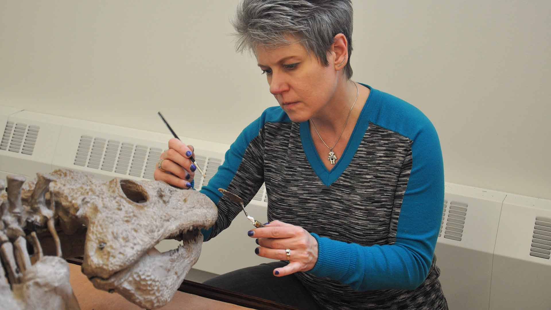 A woman uses a paintbrush to restore a part of the nose section of the skull of the object.