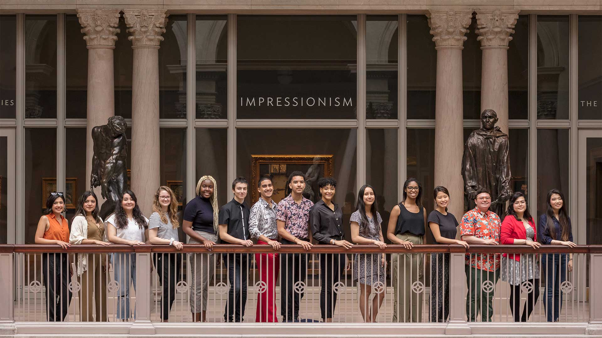 15 student interns pose in front a day-lit atrium before a gallery labeled impressionism