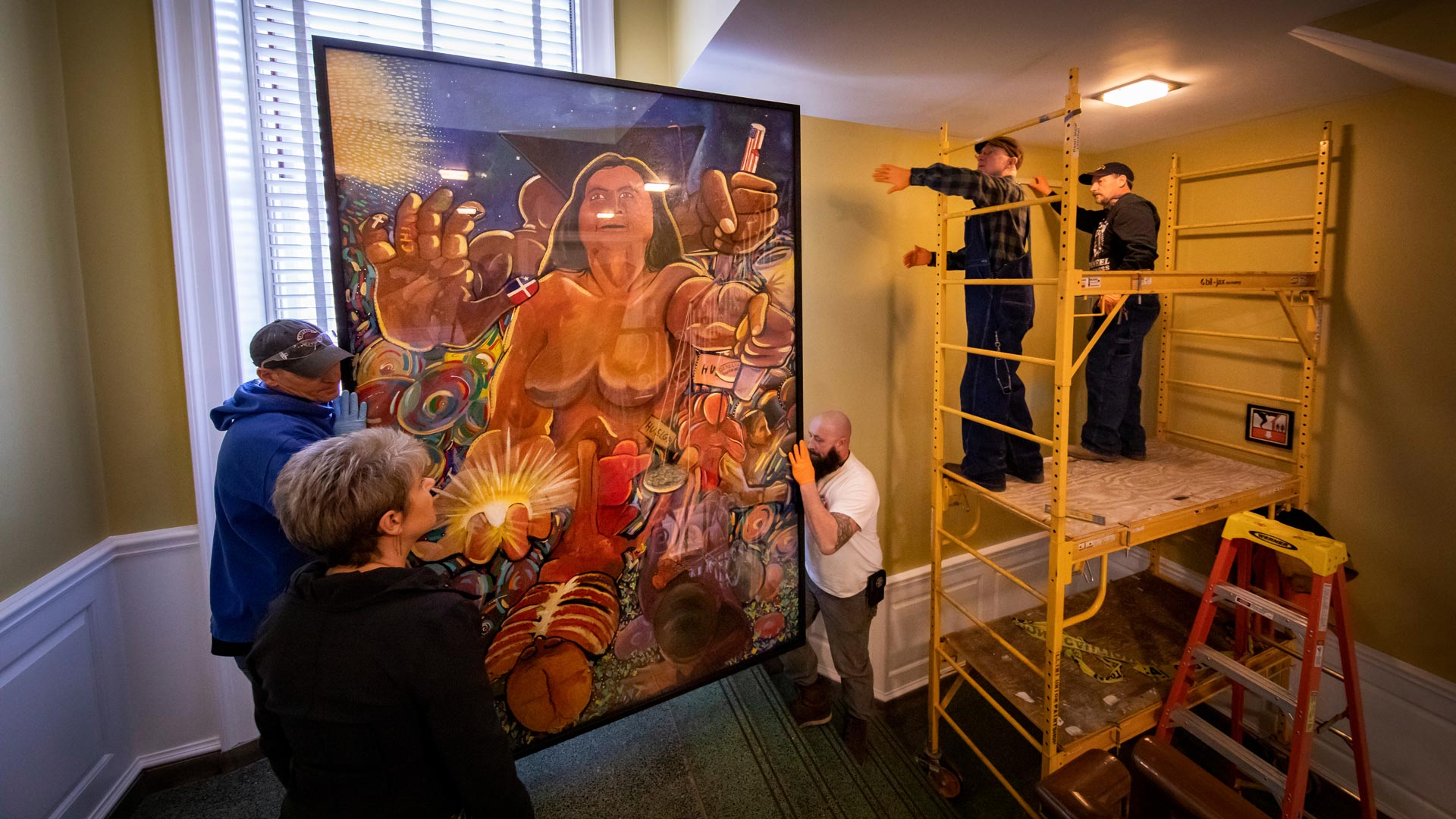 two people lifting a mural panel while two people stand on a platform to place on a wall at the Illini Union