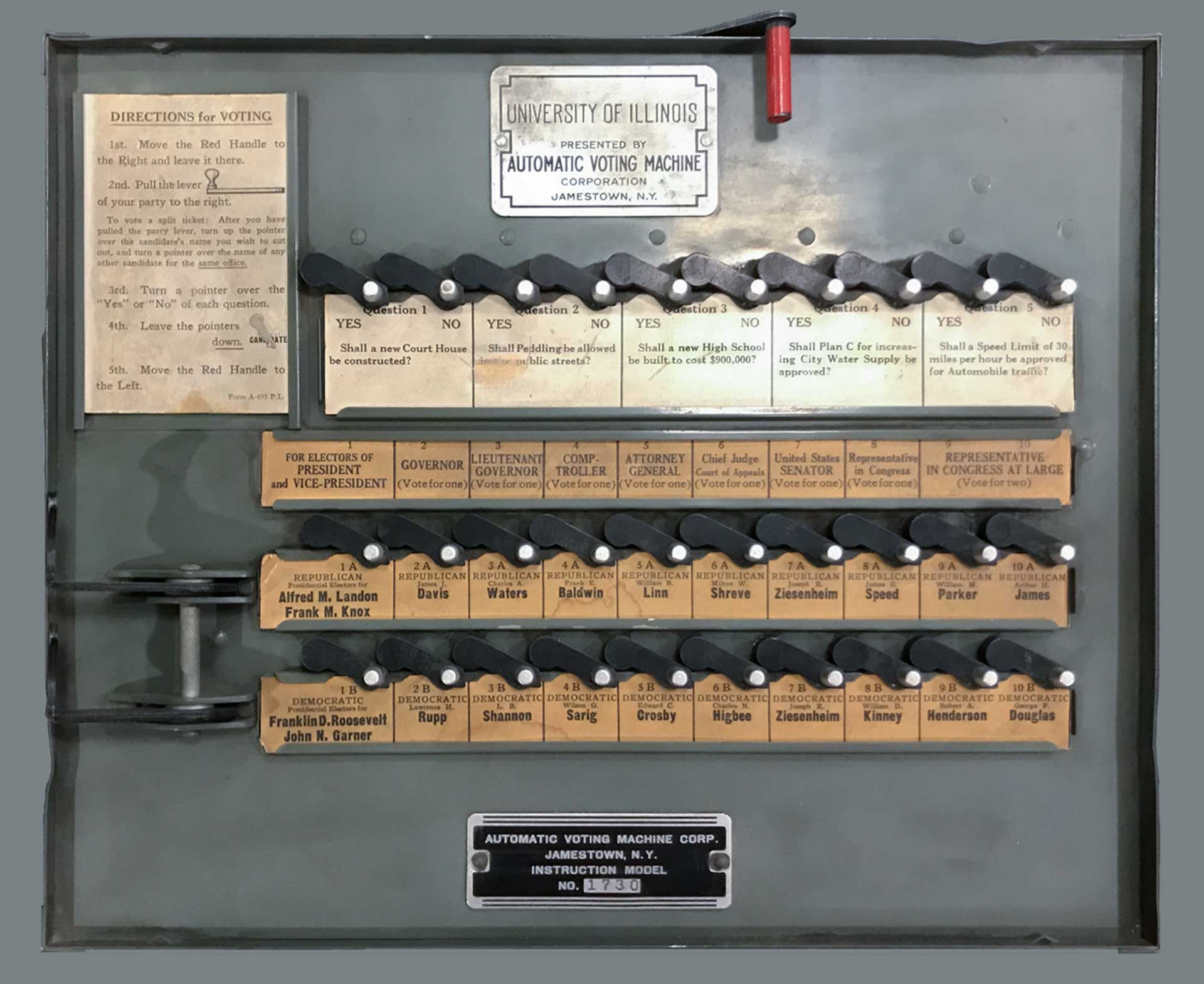 photo of an old mechanical voting machine with a University of Illinois plaque and visible referenda and candidates