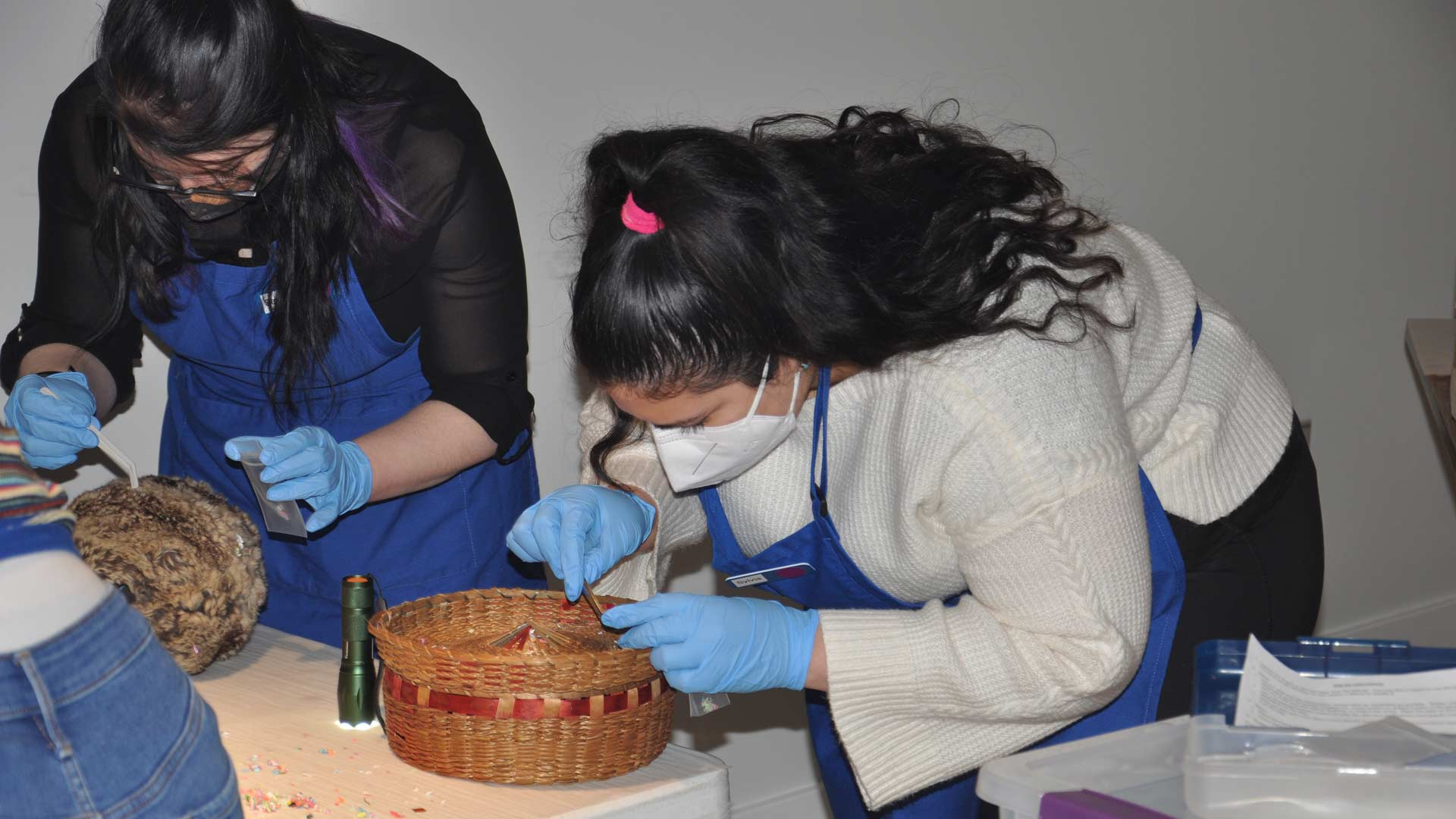 two students with gloves and masks bending over two artifacts with a tweezer