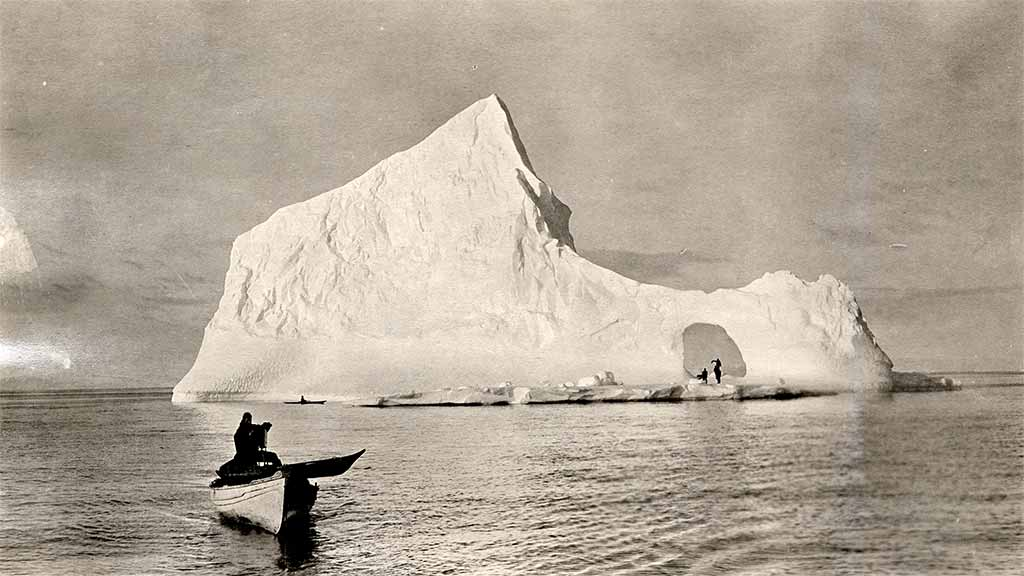 researchers in boat photograph distant iceberg with people under an arch