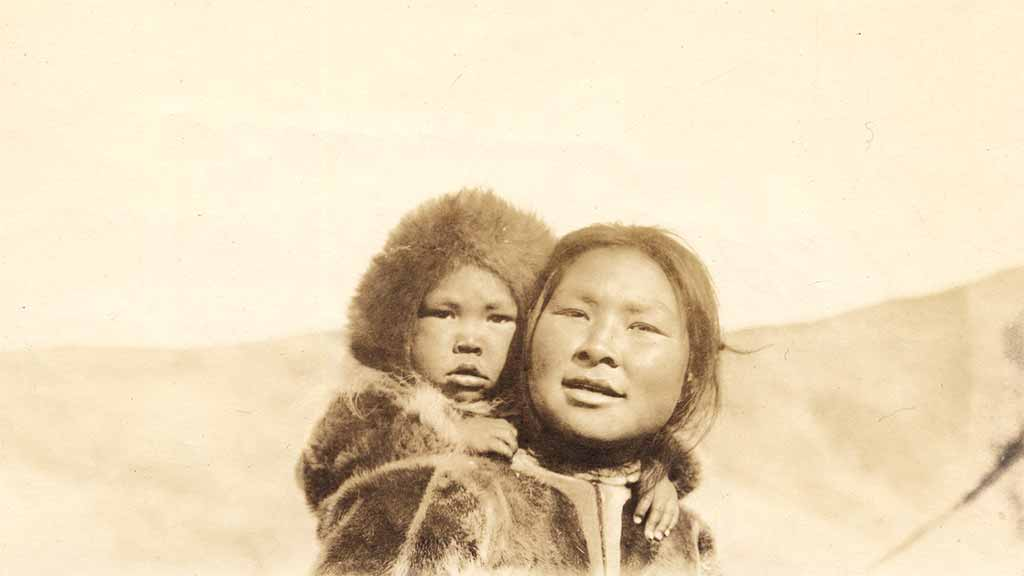 Two smiling inuit, including one small child