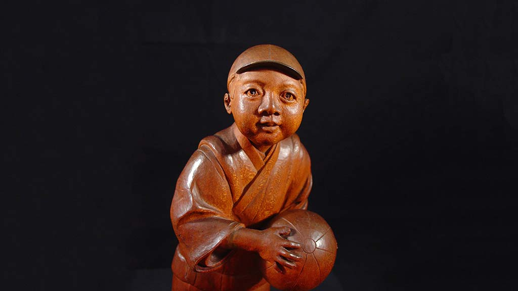 carved boy holding a volleyball