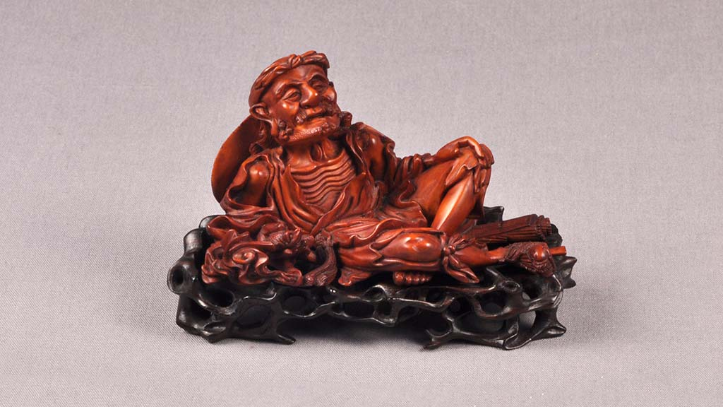 carved brush rest in the shape of an old reclining man