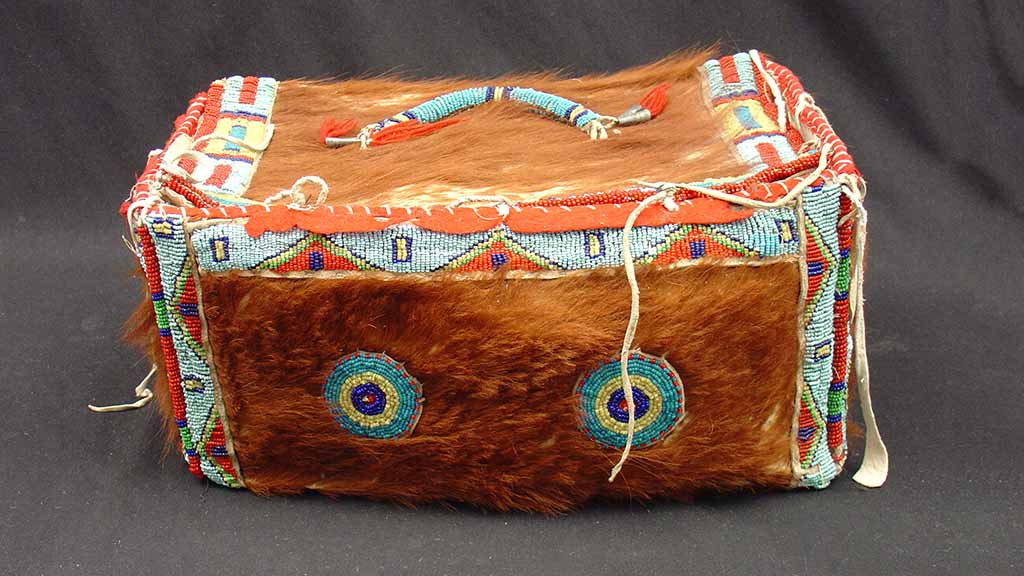 box-shaped bag with handle covered in animal fur and beads