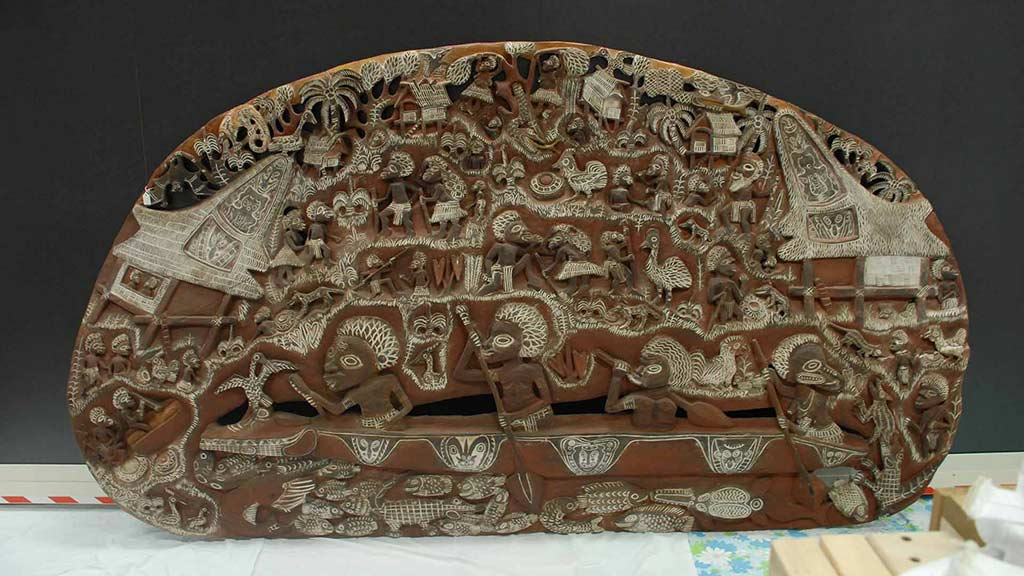 large, oval, wooden story board carved with scenes from everyday life