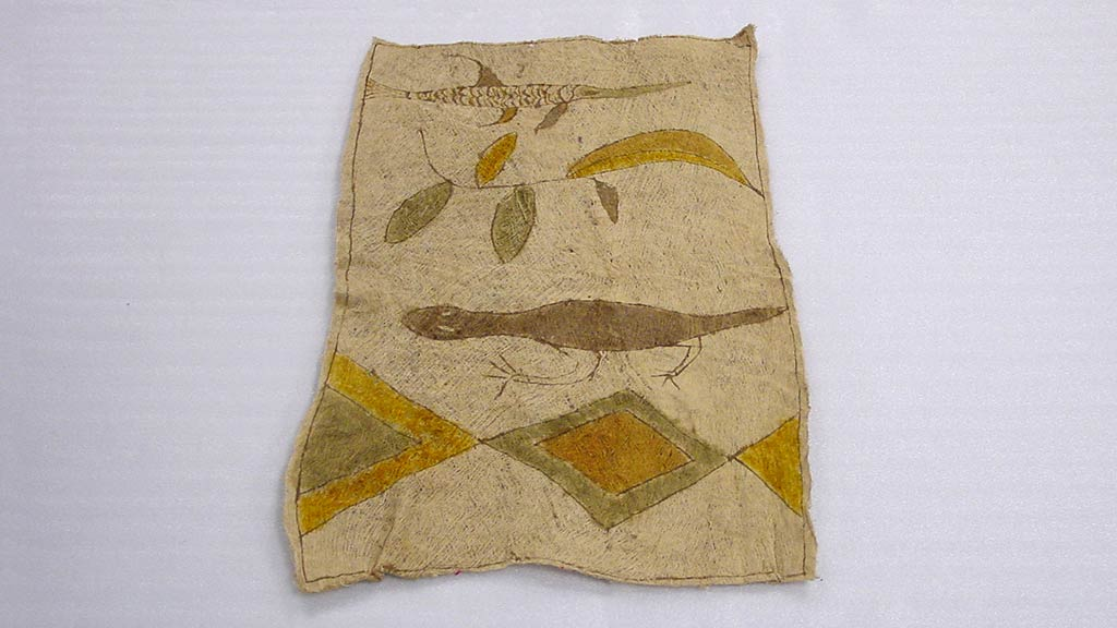 rectangular bark cloth with green, brown, and gold design