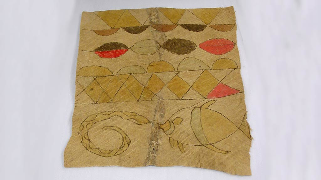 square bark cloth with gold, brown, and bright red designs