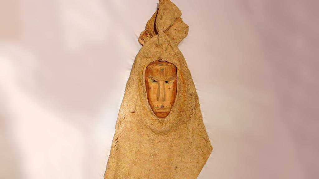 triangular bark cloth mask with human-looking wooden face