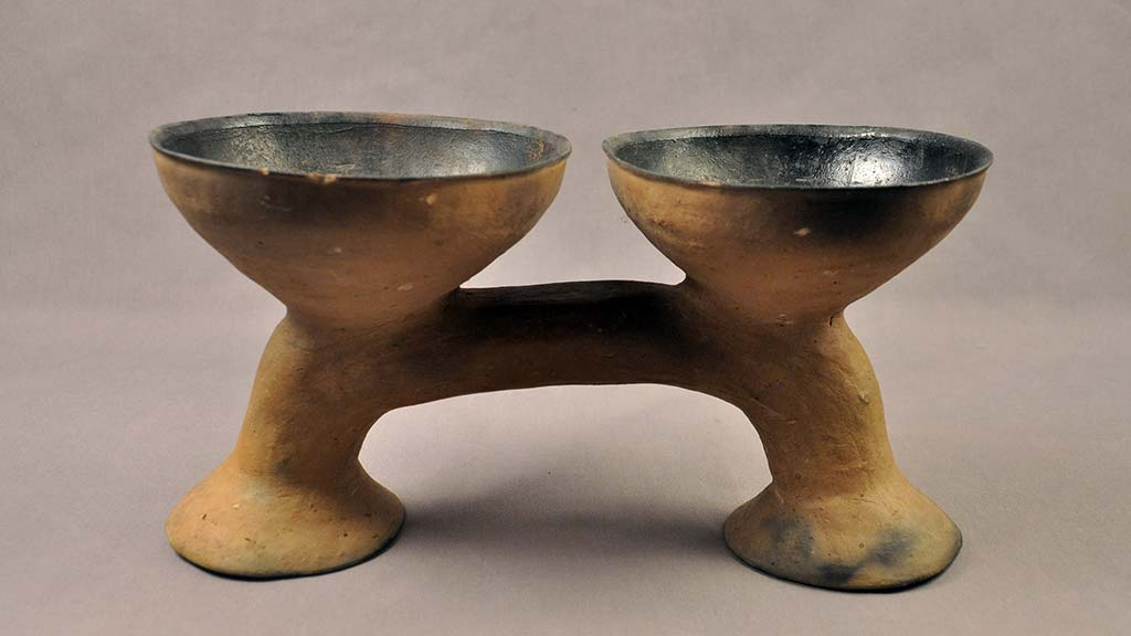 two earthenware bowls connected by a stand