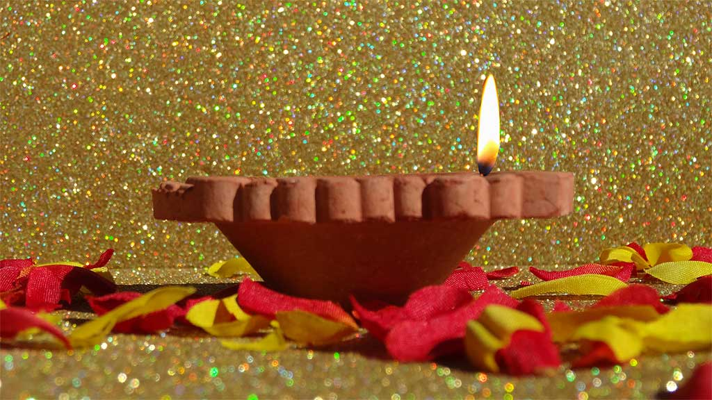 small terracotta burner with flame on a bed of petals against a gold backdrop