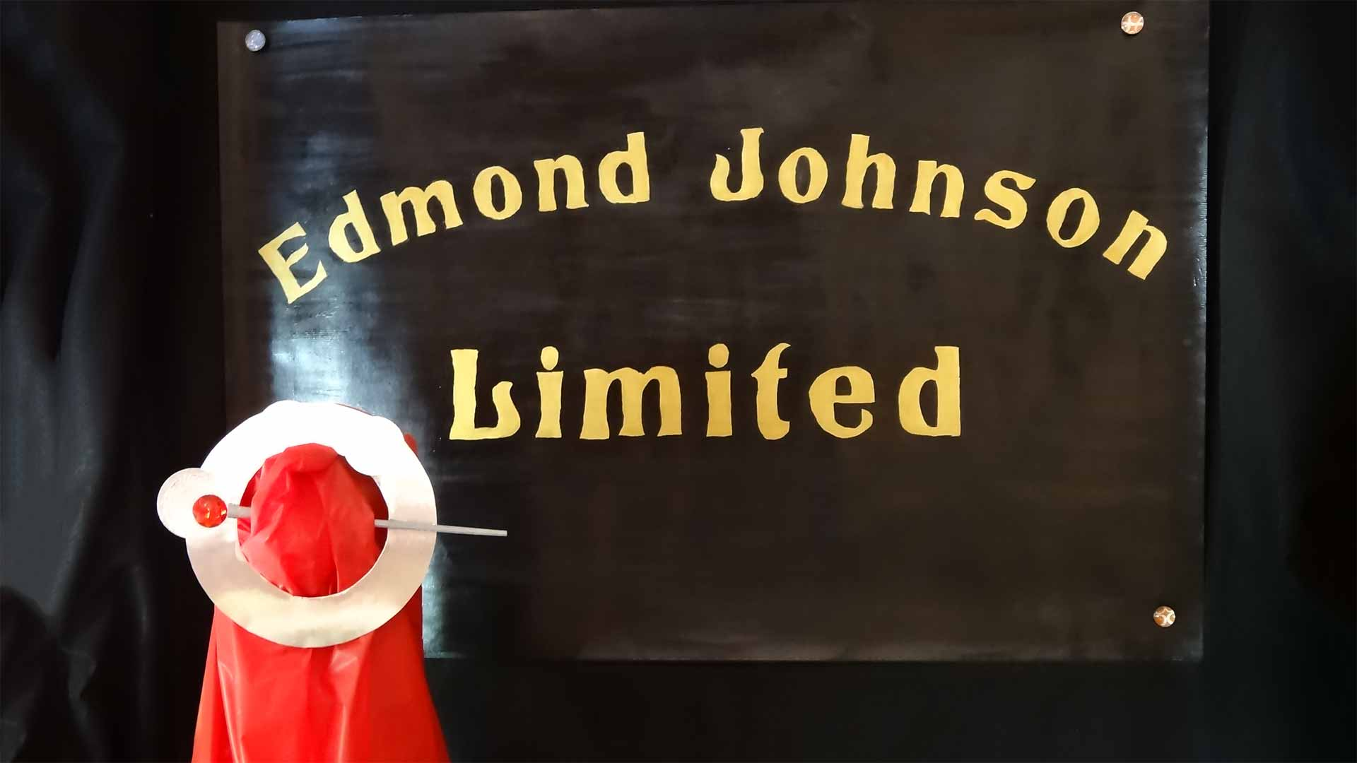 "sign reading ""edmond johnson limited"" with a piece of fabric and pin brooch"