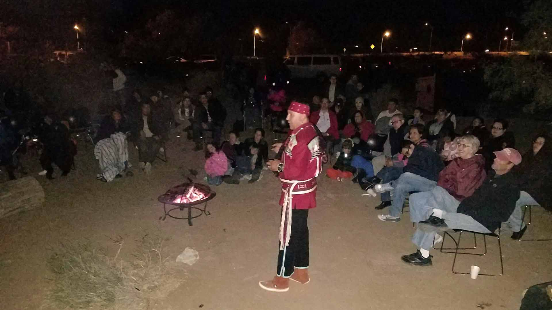 Alex Mares stands in front of a fire pit surrounded by people seeted in camping chairs with coats and blankets