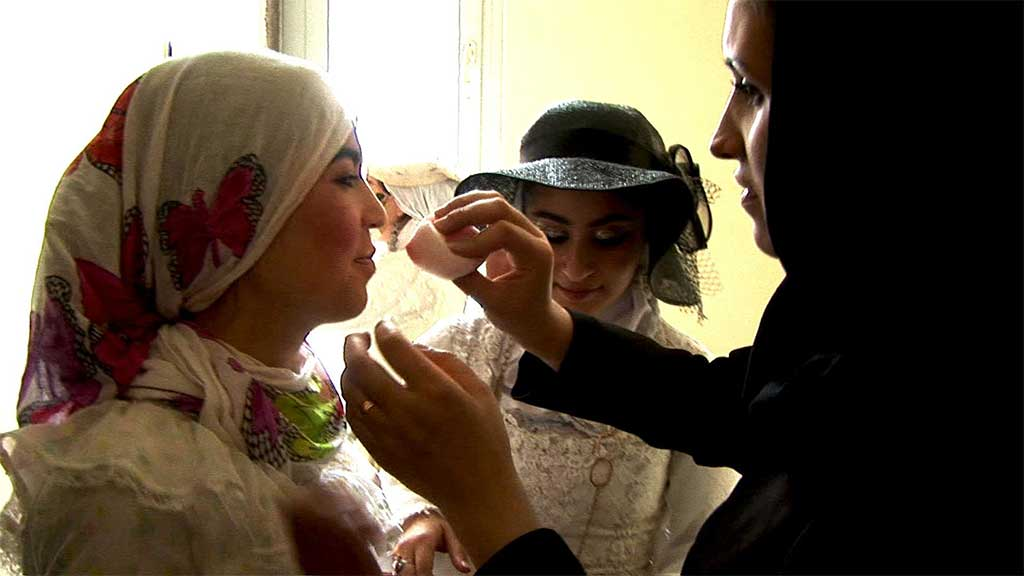 a woman applies makeup to an actress wearing a headscarf