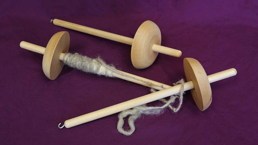 3 wooden drop spindles, one with yarn