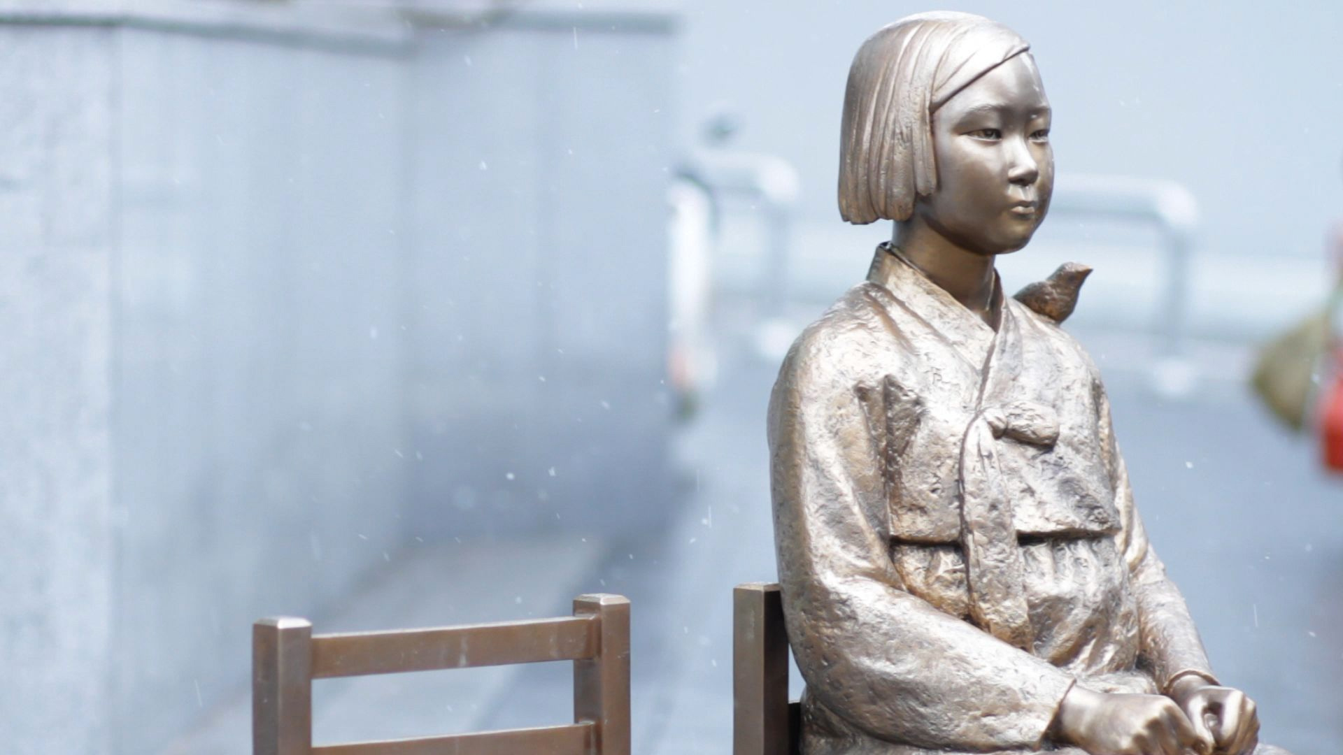 A statue of a Korean girl sitting in a chair with a bird on her shoulder, also known as the Statue of Peace