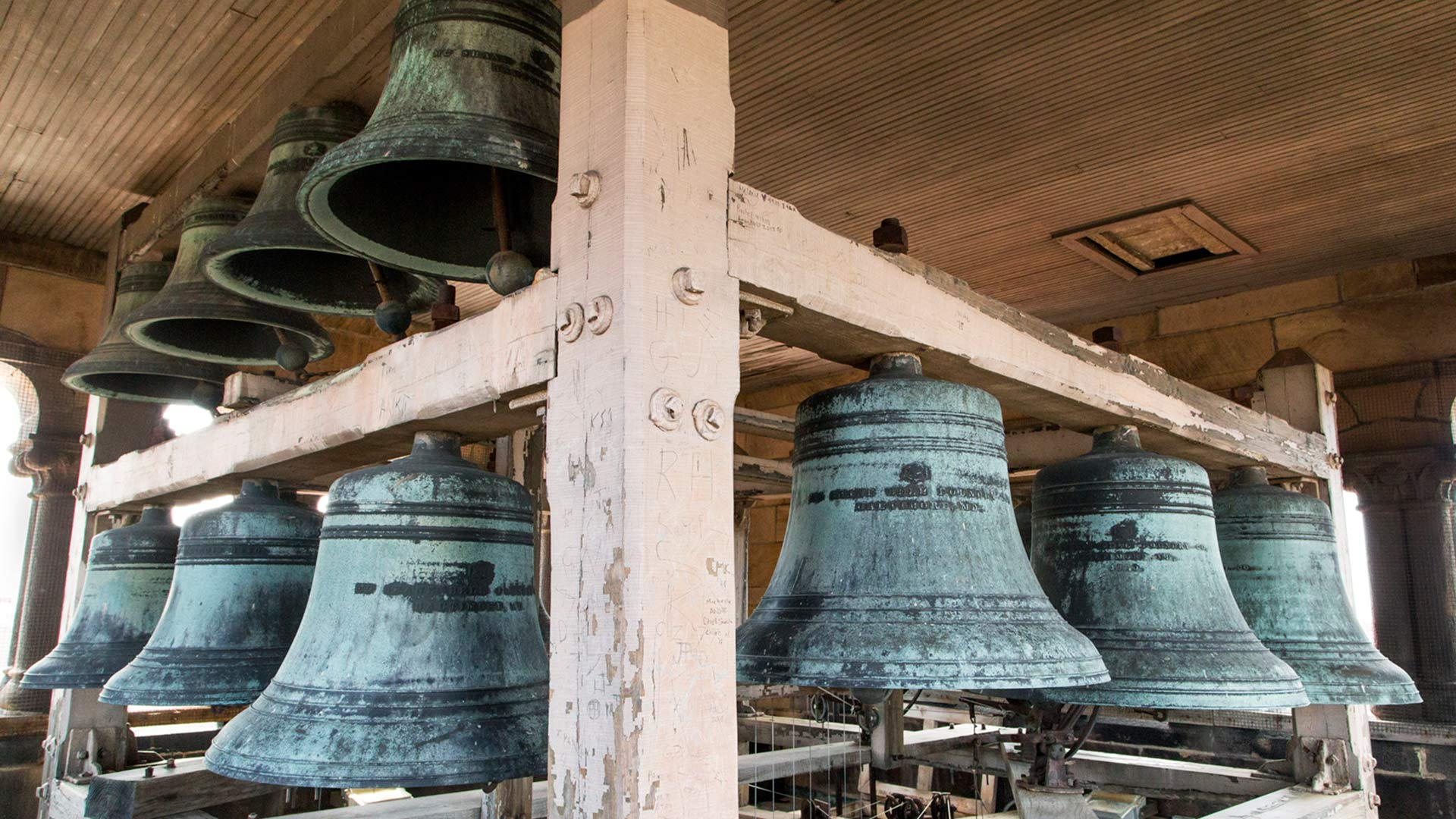 Large bells, textured bluish gray hanging from wooden beams