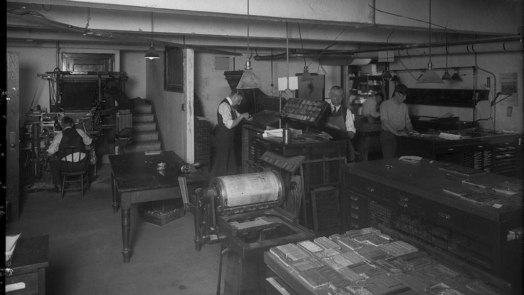 A black and white image of five men working on printing presses in an underground room 8/16/2018