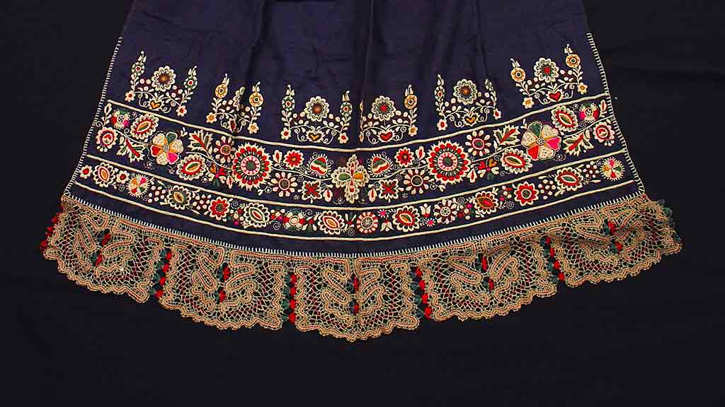 Elaborate embroidery and lace on the bottom of a navy blue skirt. The embroidery and lace are floral patterns of cream, red, green, and pink colors.  8/26/2018