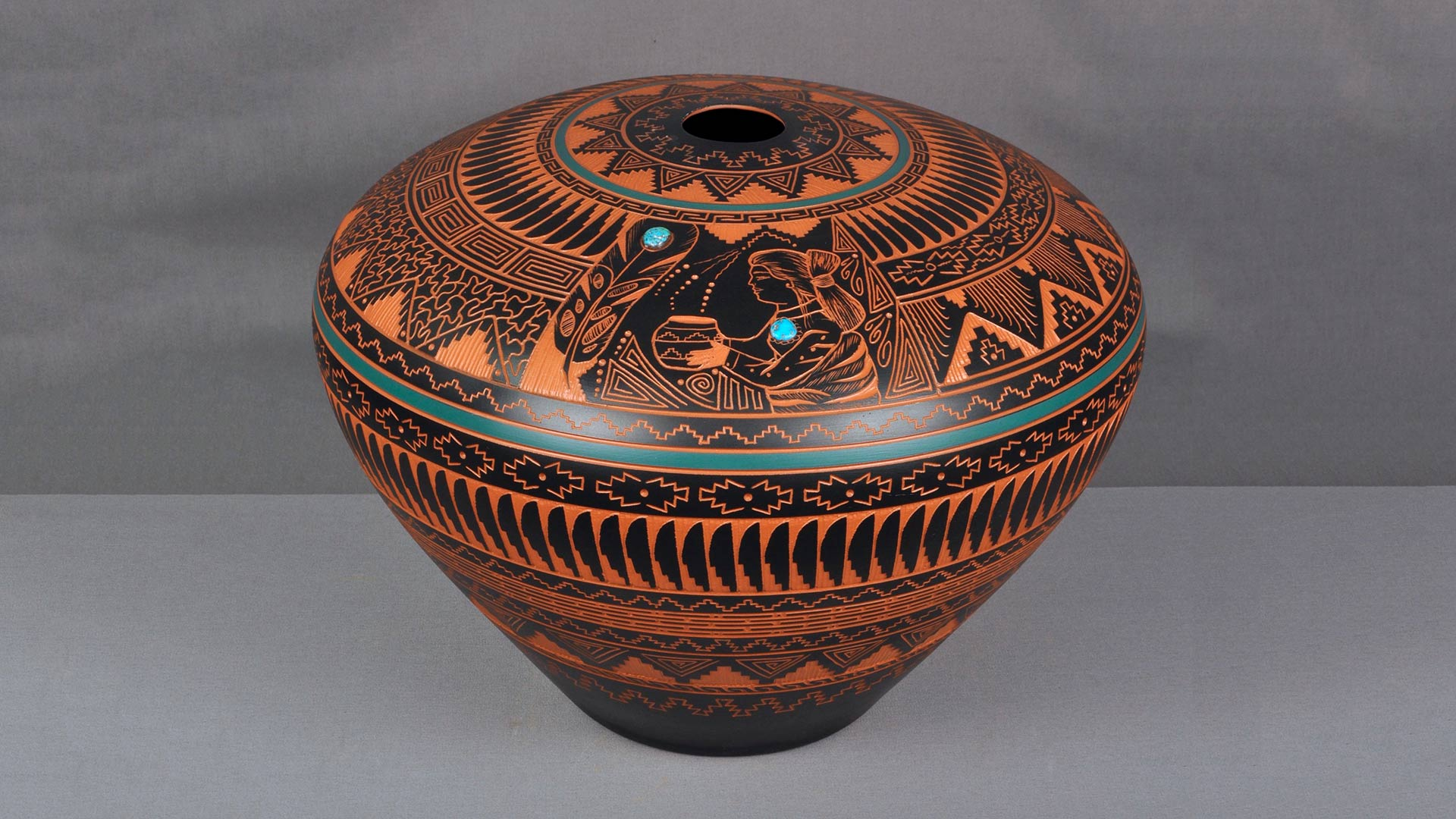 An orange clay vessel decorated with intricate black and turquoise patterns.