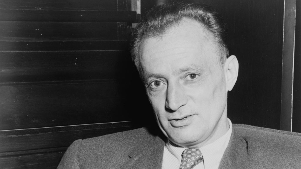 Nelson Algren sitting in a suit looking at the camera and holding a paper 12/20/2018