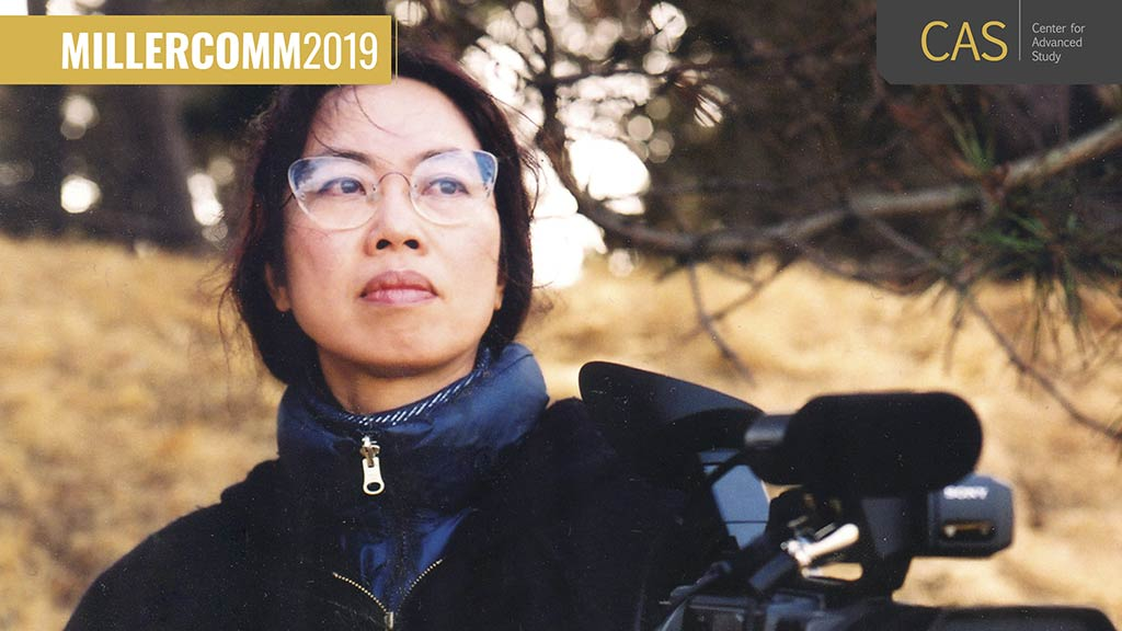A woman with glasses from Asian descent stands outside in cool weather and gazes off camera 4/3/2019