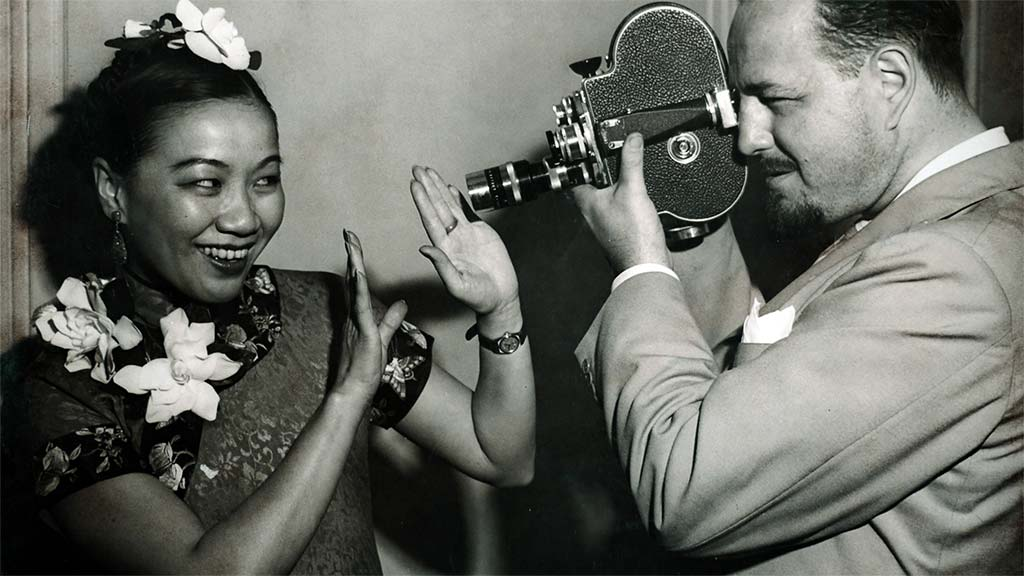 1940s photo of a man with handheld video camera pointing at smiling woman with flowers 4/9/2019