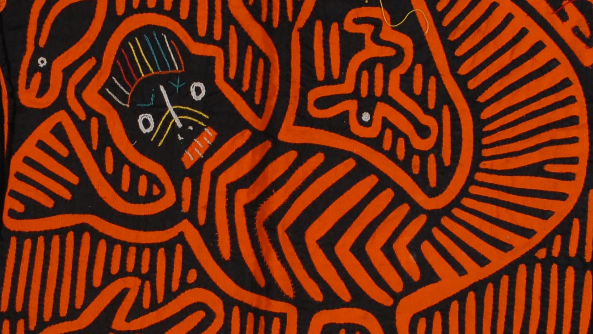 geometric pattern in orange and black of a small animal on fabric