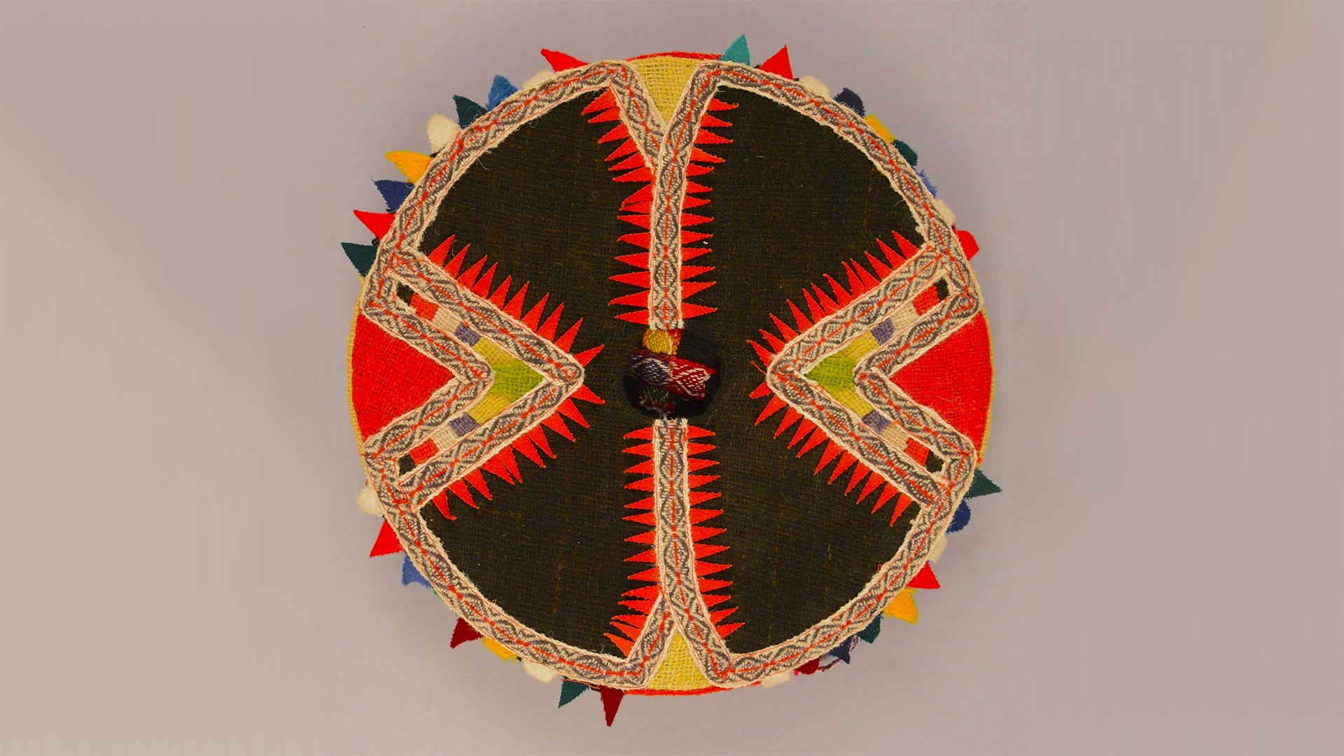 top view of a flat round woven hat with red and black pointy design