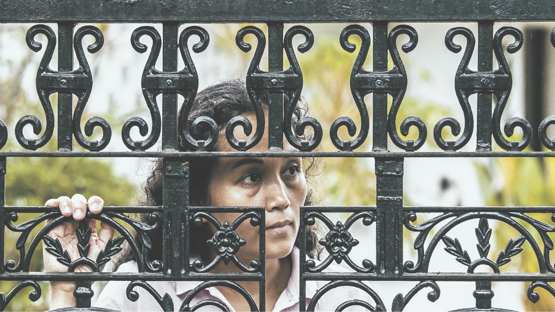 woman staring through black fence