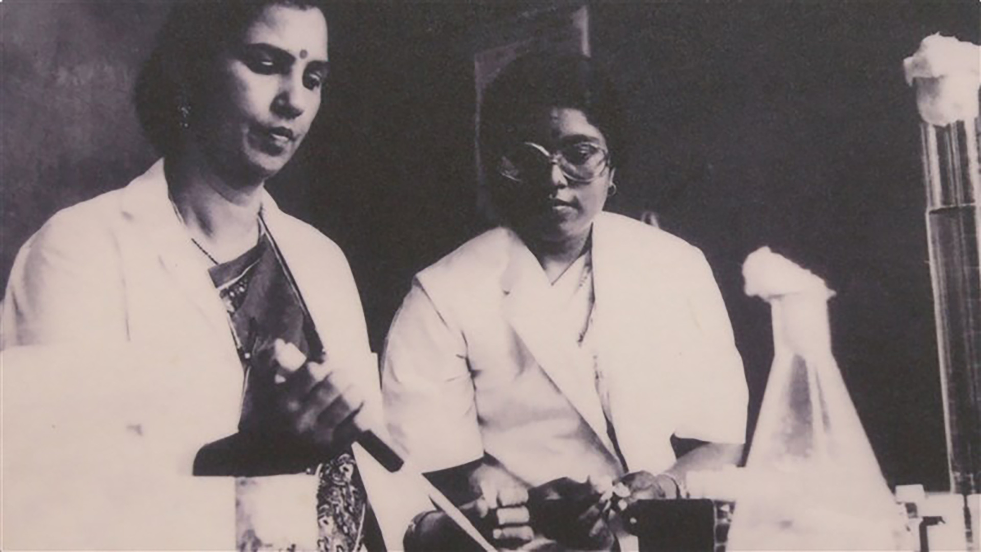 vintage photo of two Indian women in lab coats performing an experiment